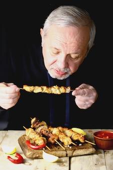 L'uomo sta mangiando uno spiedino di pollo