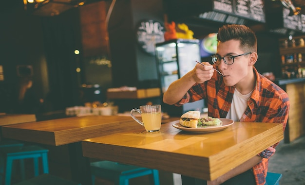 L'uomo sta mangiando in un ristorante e gustando cibo delizioso