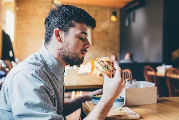 L'uomo sta mangiando in un ristorante e sta godendo il cibo delizioso