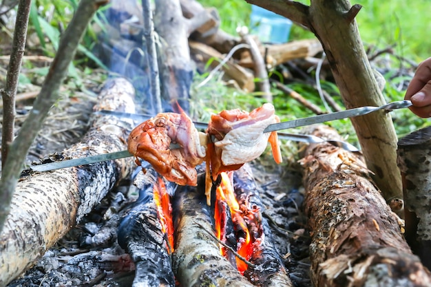 L'uomo sta friggendo il pollo sul fuoco aperto. grigliare nel bosco. turista che mangia all'aperto.