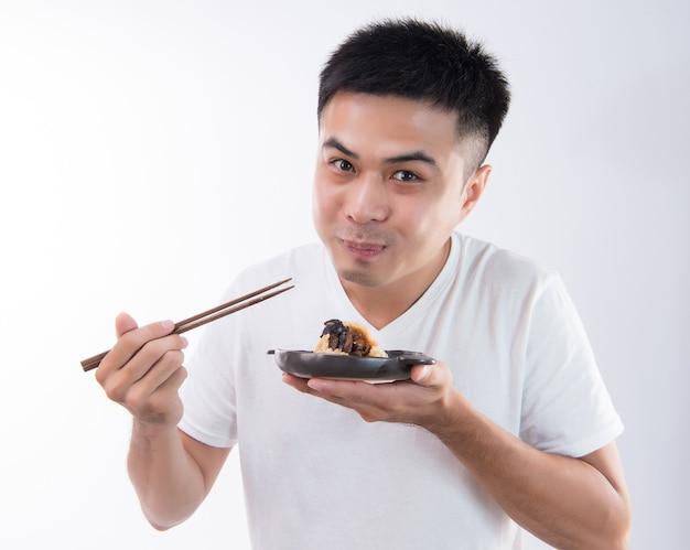 Un uomo mangerà deliziosi zongzi (gnocchi di riso) su dragon boat festival, cibo tradizionale asiatico, sfondo bianco