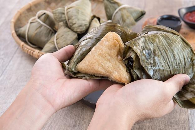 Un uomo mangerà zongzi o gnocchi di riso al dragon boat festival, cibo tradizionale asiatico