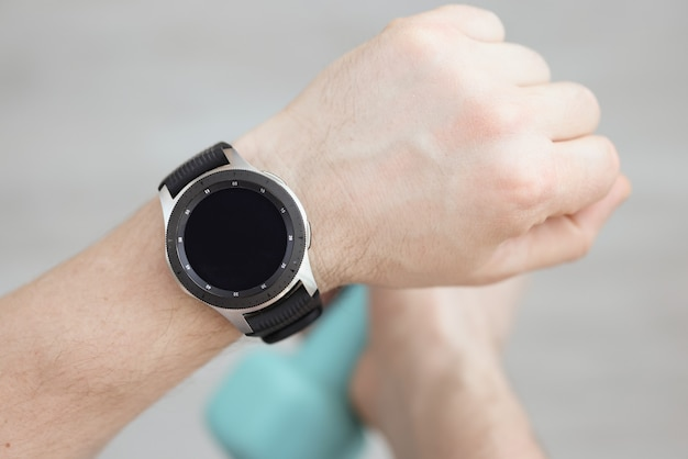 L'uomo è la mano indossa un orologio intelligente, mentre l'altra mano tiene il manubrio