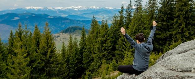 Un uomo è in alto sulle montagne contro il cielo, celebra la vittoria, alzando le mani.