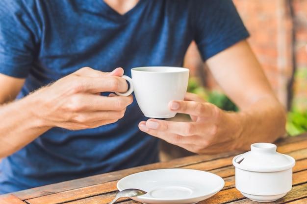 L'uomo sta tenendo la tazza di tè al limone