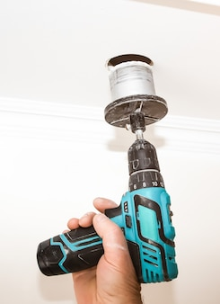 L'uomo tiene in mano un trapano elettrico. grande buco nel soffitto. lavori di riparazione di manutenzione nell'appartamento. restauro al chiuso.