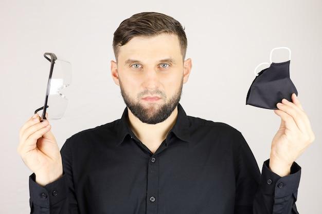 L'uomo tiene in mano occhiali medici e una maschera protettiva su uno sfondo bianco