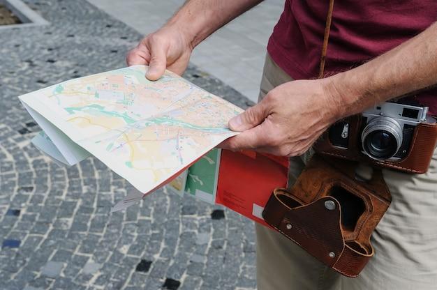 Un uomo tiene in mano una mappa turistica
