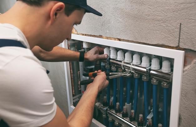 L'uomo sta installando il sistema di riscaldamento in casa