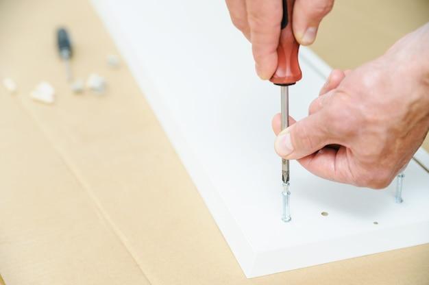 Un uomo sta installando i bulloni del connettore di giunzione nel pannello del mobile.
