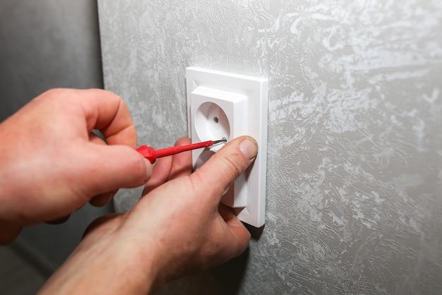 L'uomo sta installando la presa. lavori di riparazione di manutenzione dell'elettricità nell'appartamento. restauro al chiuso.