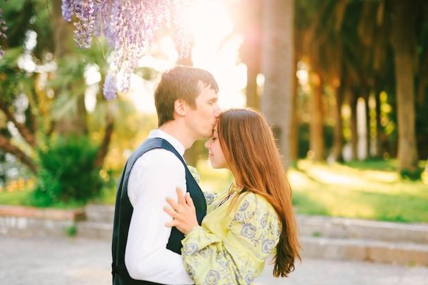 L'uomo sta baciando una donna sulla fronte sotto un albero di glicine in fiore nel parco