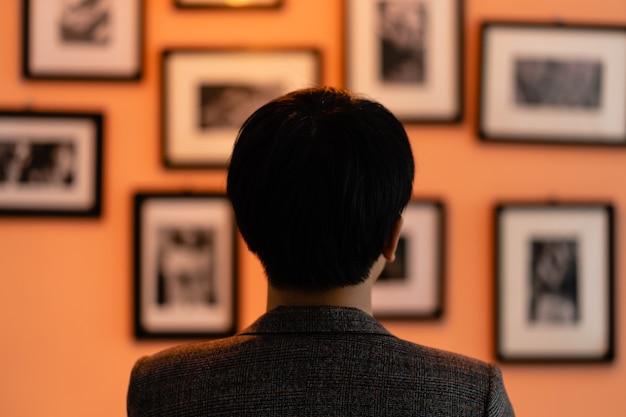 L'uomo sta guardando le foto sul muro