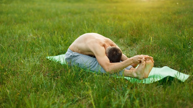 L'uomo sta facendo yoga nel parco