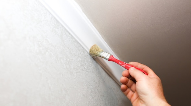 L'uomo sta dipingendo battiscopa in gesso con pennello sul soffitto. lavori di riparazione di manutenzione nell'appartamento. restauro al chiuso. pannello in cartongesso.