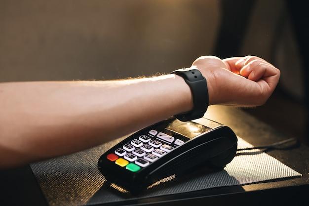 L'uomo paga con un orologio intelligente con tecnologia contactless nfc persona paga in un bar