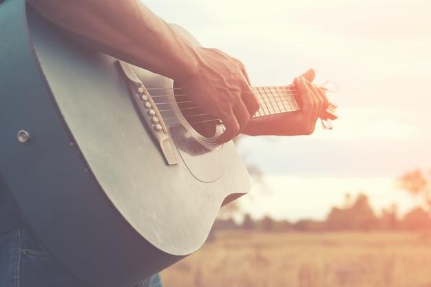 Un uomo sta giocando la chitarra in campo in erba al giorno di relax