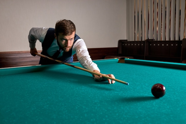 L'uomo sta giocando a biliardo, mira a sparare alla palla da biliardo. bel ragazzo tiene le mani sul tavolo da biliardo. biliardo