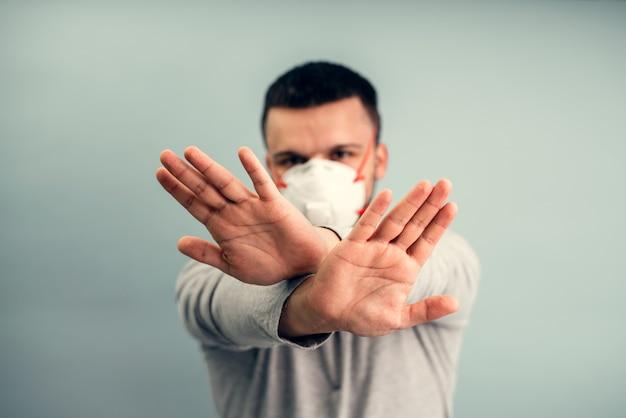 Un uomo indossa una maschera protettiva. protezione respiratoria dal coronavirus. dispositivi di protezione individuale per una pandemia di un'infezione virale. covid19.