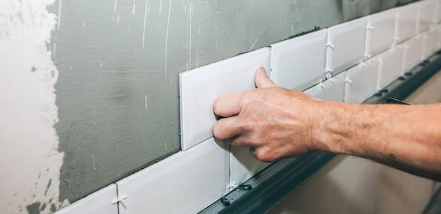 L'uomo sta mettendo piastrelle bianche sul cemento grigio. ristrutturazione lavori di riparazione di manutenzione nell'appartamento. restauro al chiuso. lavori in corso.