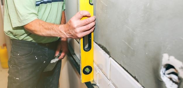 L'uomo sta mettendo piastrelle bianche sul cemento grigio. ristrutturazione lavori di riparazione di manutenzione nell'appartamento. restauro con livella a bolla per interni. lavori in corso. l'uomo tiene in mano una livella a bolla d'aria.