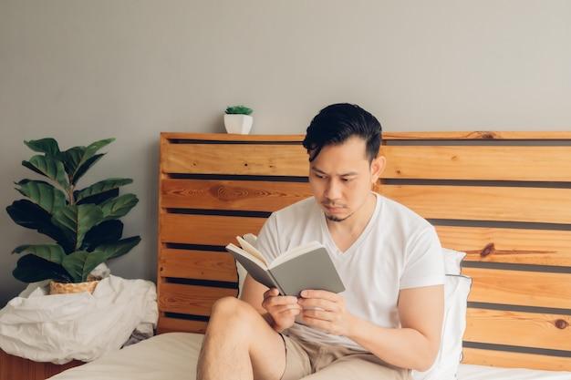 L'uomo sta leggendo il libro sul suo letto nel tardo pomeriggio.