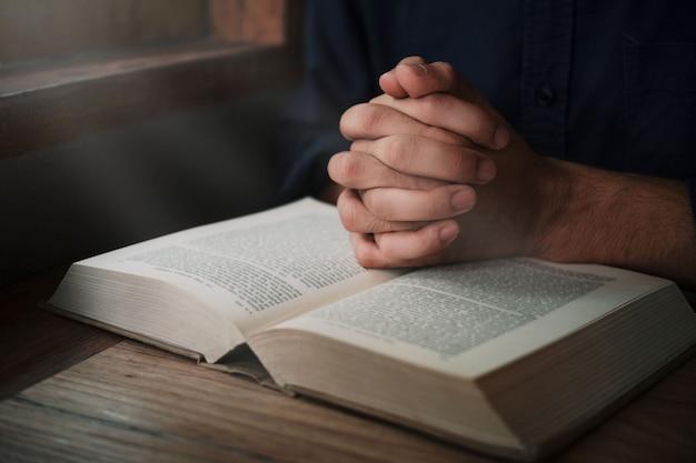 L'uomo sta leggendo e pregando la scrittura o la sacra bibbia su un tavolo di legno con spazio per le copie. religione, credo concetto.