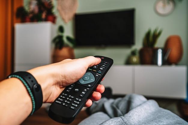 Un uomo si sta rilassando sul divano e usa il telecomando e guarda la tv con interni accoglienti