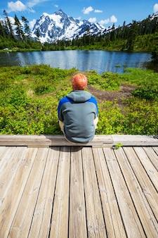 Un uomo sta riposando a suo agio in riva al lago calmo. vacanza relax