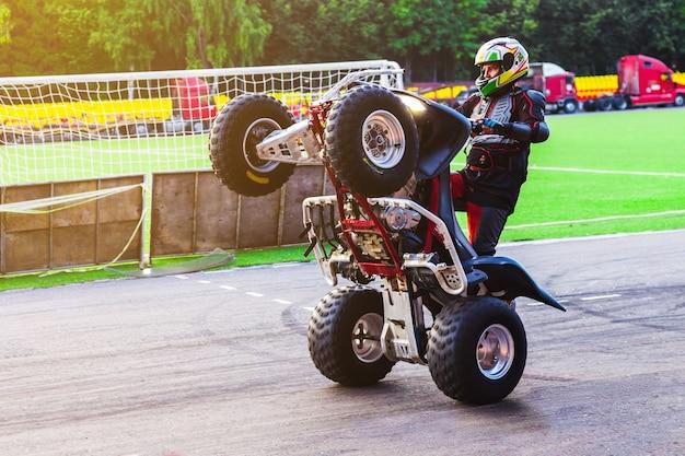 Un uomo sta guidando un atv sulle ruote posteriori. impennata. cheboksary, russia, 2/9/2017