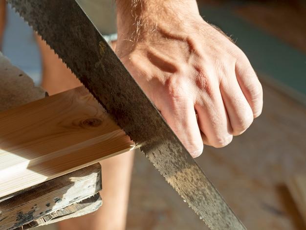 Un uomo sta segando una tavola con una sega a mano. concetto di lavorazione del legno. avvicinamento