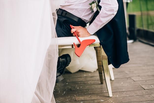 L'uomo è seduto su una sedia tenendo le scarpe femminili simbolo della mano