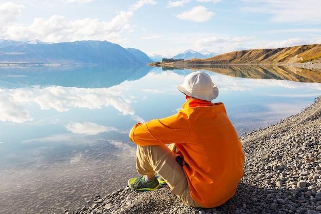 Un uomo è seduto a suo agio in riva al lago calmo. vacanza relax