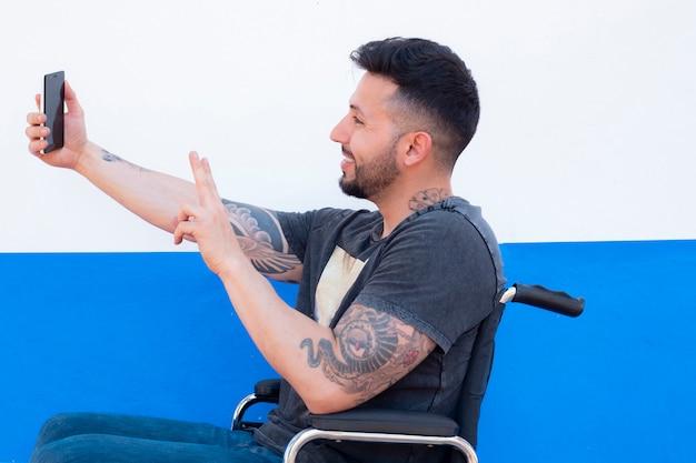 L'uomo è seduto su una sedia a rotelle, con cellulare