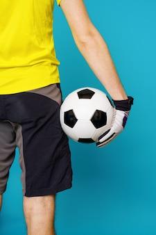 L'uomo è fan di socccer in maglietta gialla con pallone da calcio su sfondo blu