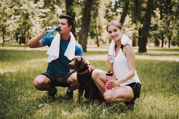 L'uomo accarezza l'animale domestico e l'acqua potabile. giornata di sole estivo.