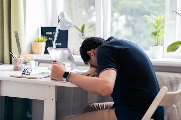 L'uomo è stanco e dorme sulla tastiera del laptop
