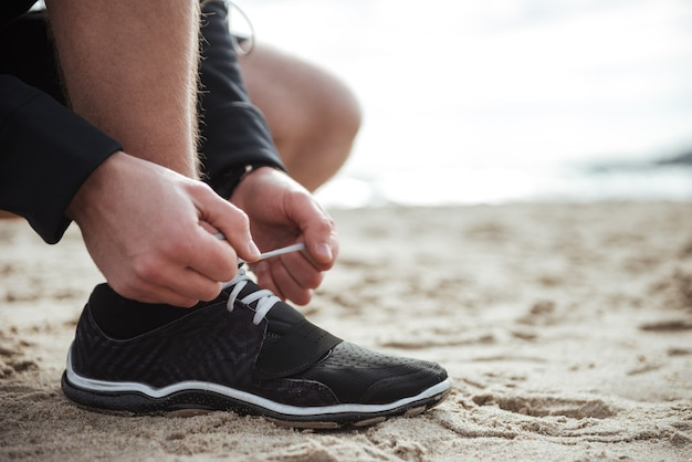 L'uomo si sta allacciando le scarpe mentre è in piedi sulla sabbia primo piano close