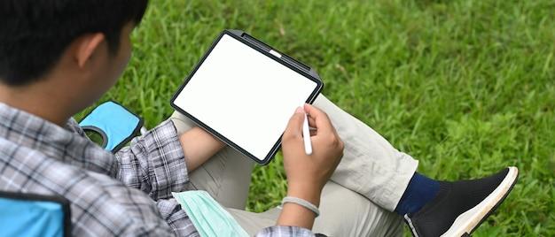 Un uomo sta utilizzando un tablet computer mentre è seduto su una sedia da campeggio sul campo in erba.