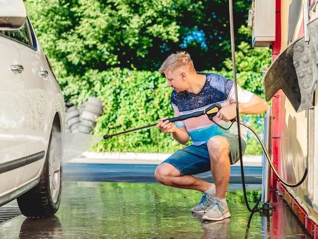 L'uomo sta lavando l'auto con acqua ad alta pressione