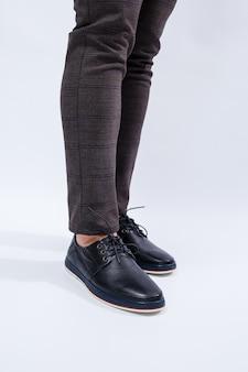 Un uomo indossa scarpe nere classiche in pelle naturale su pizzo, scarpe da uomo in stile business. foto di alta qualità
