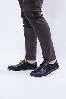 Un uomo indossa scarpe nere classiche fatte di pelle naturale su pizzo, scarpe da uomo in stile business