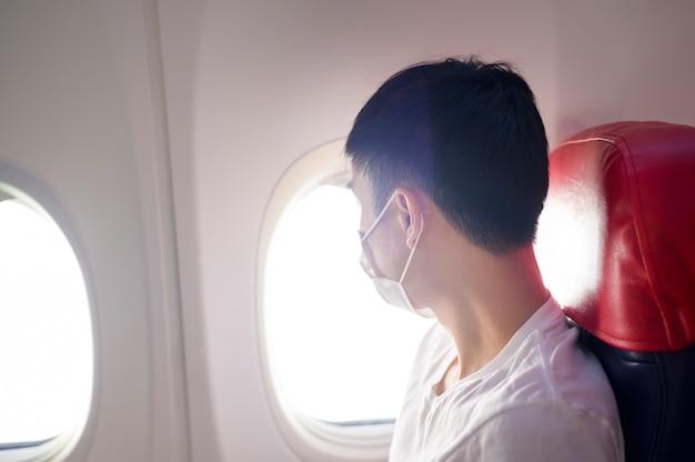 L'uomo indossa una maschera protettiva a bordo dell'aereo, viaggia sotto la pandemia covid-19