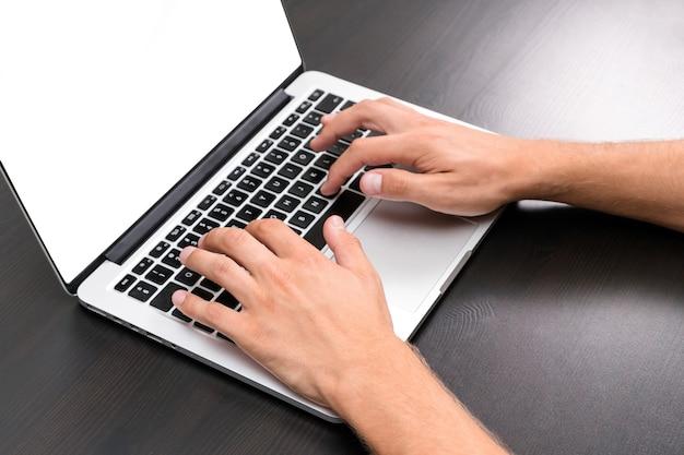 Un uomo sta lavorando utilizzando un computer portatile su un tavolo di legno d'epoca.