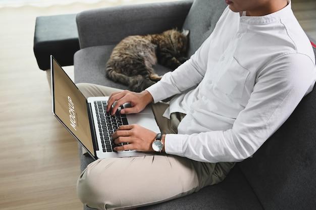 L'uomo sta lavorando al computer portatile mentre era seduto sul divano