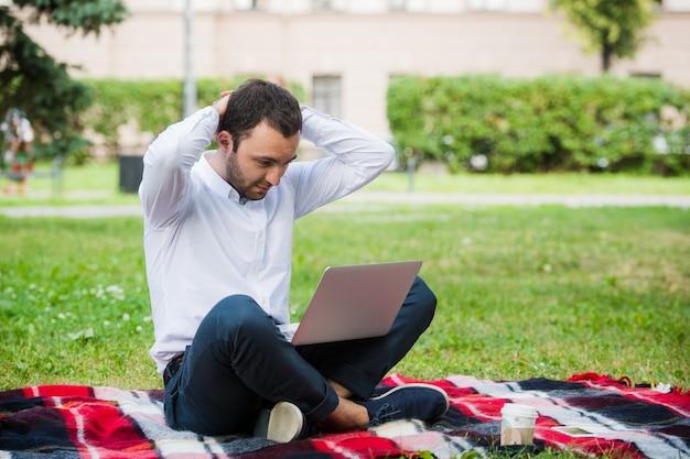 Un uomo sta lavorando utilizzando il computer portatile al parco