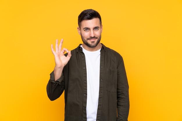 Uomo su sfondo giallo isolato che mostra un segno ok con le dita