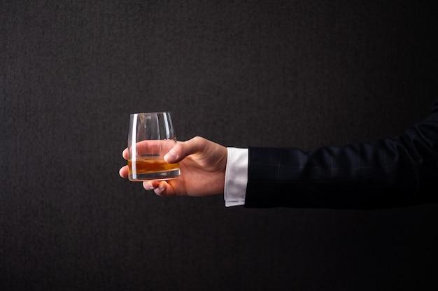 Un uomo in giacca tiene in mano un bicchiere di whisky.