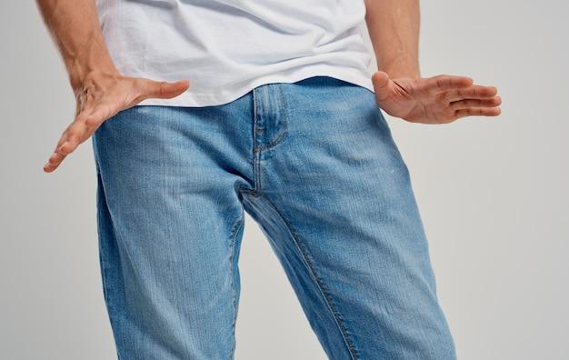 Un uomo in jeans gesticola con le mani sotto la cintura su uno sfondo chiaro. foto di alta qualità