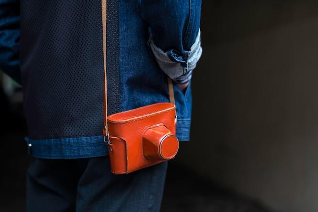 Uomo in giacca di jeans con fotocamera a pellicola vintage in una custodia in pelle